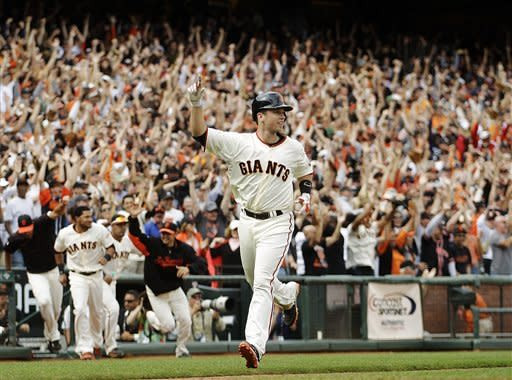 San Francisco Giants' Buster Posey celebrates as he scores the game-winning run scored on a hit by Angel Pagan against the Cincinnati Reds in the ninth inning of a baseball game, Sunday, July 1, 2012, in San Francisco. The Giants won 4-3. (AP Photo/Ben Margot)