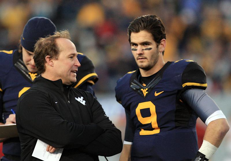 West Virginia coach Dana Holgorsen speaks with quarterback Clint Trickett (9) during a timeout in the second quarter of their NCAA college football game against Iowa State in Morgantown, W.Va., on Saturday, Nov. 30, 2013