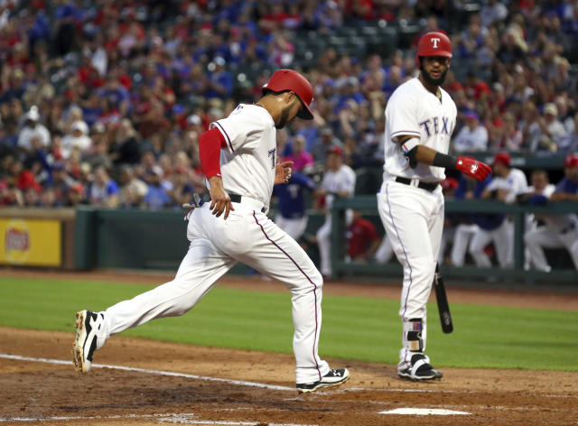 Texas Rangers Isiah Kiner-Falefa (9) scores on a wild pitch by Oakland Athletics starter Trevor Cahill during the third inning of a baseball game Monday, April 23, 2018, in Arlington, Texas. (AP Photo/Richard W. Rodriguez)