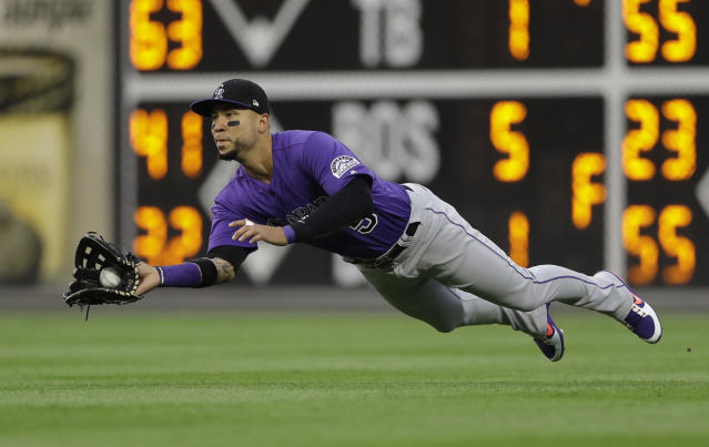 Colorado Rockies right fielder Carlos Gonzalez dives for and catches a fly ball hit by Philadelphia Phillies' Jorge Alfaro during the third inning of a baseball game Wednesday, June 13, 2018, in Philadelphia. (AP Photo/Matt Slocum)
