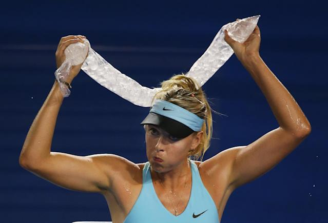 MELBOURNE, AUSTRALIA - JANUARY 14: Maria Sharapova of Russia cools off during a break in her first round match against Bethanie Mattek-Sands of the United States during day two of the 2014 Australian Open at Melbourne Park on January 14, 2014 in Melbourne, Australia. (Photo by Scott Barbour/Getty Images)