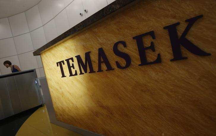 Woman passes a logo of state investor Temasek Holdings at their office in Singapore