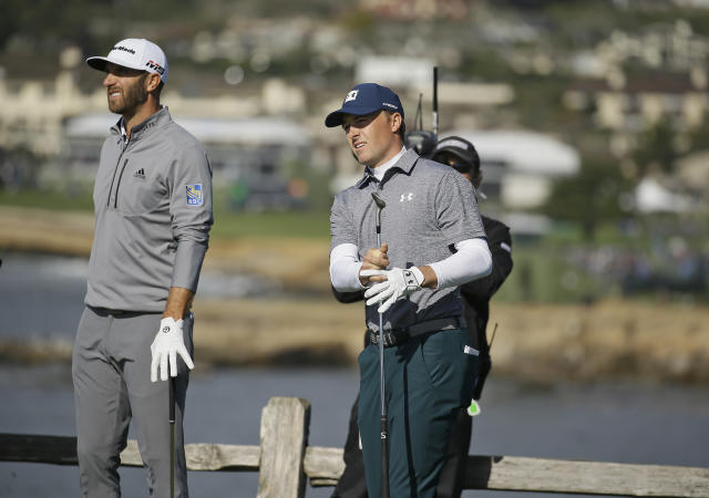 Jordan Spieth, right, follows his shot from the seventh tee of the Pebble Beach Golf Links as Dustin Johnson looks on during the third round of the AT&T Pebble Beach Pro-Am golf tournament Saturday, Feb. 9, 2019, in Pebble Beach, Calif. (AP Photo/Eric Risberg)