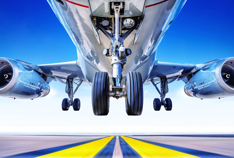 A view from underneath as a plane takes off from a runway