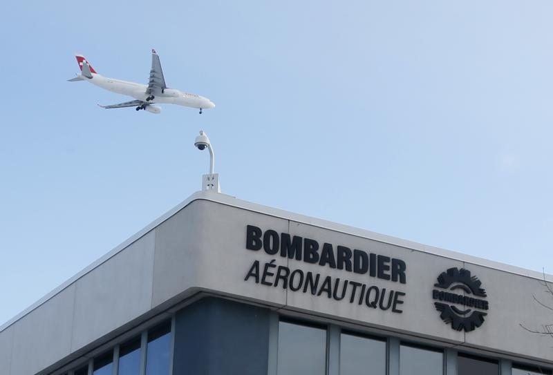 A plane flies over a Bombardier plant in Montreal