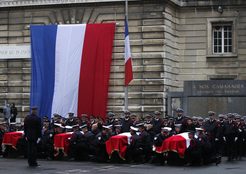 Police officers carry the coffins of the four victims of last week's knife attack during a ceremony in the courtyard of the Paris police headquarters Tuesday, Oct. 8, 2019 in Paris. France's presidency says the four victims of last week's knife attack at the Paris police headquarters will be posthumously given France's highest award, the Legion of Honor. (AP Photo/Francois Mori)