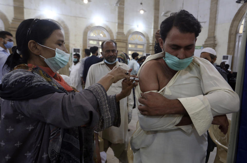 A man receives a shot of the Sinovac COVID-19 vaccine from a health worker, at a vaccination center in Karachi, Pakistan, Monday, Aug. 2, 2021. (AP Photo/Fareed Khan)