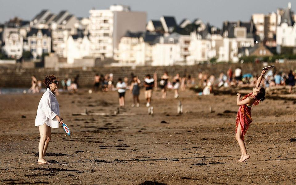 Two women play beach ball on a beach by the sea in Saint-Malo - AFP
