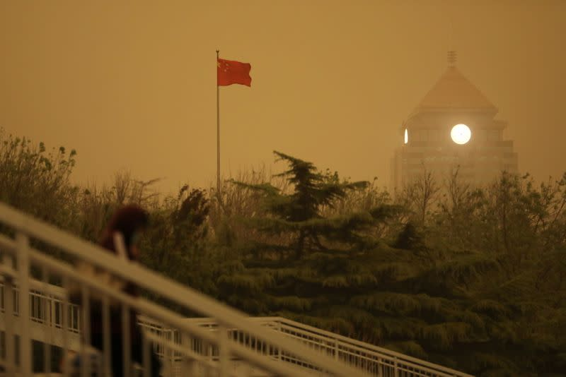 Pedestrian walks near a Chinese flag amid a duststorm in Beijing