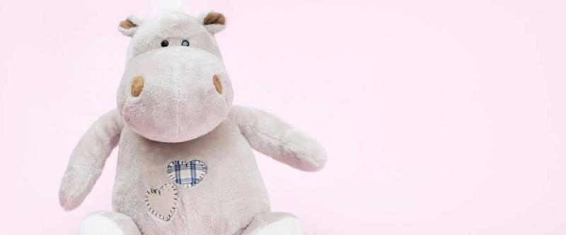 Hippo toy on a pink background, copy space
