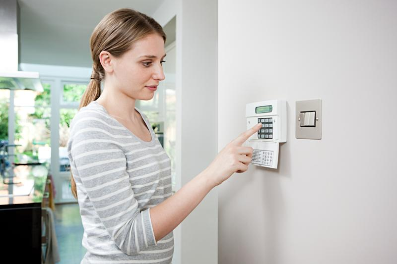 A woman setting a security alarm.