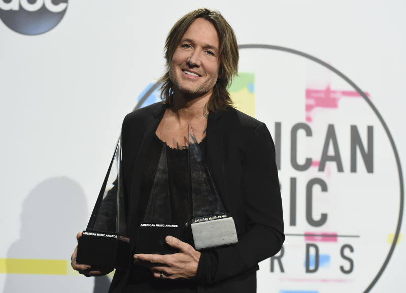 "Keith Urban poses in the press room with the awards for favorite male artist country, favorite song country for ""Blue Ain't Your Color"" and favorite album country for ""Ripcord"" at the American Music Awards at the Microsoft Theater on Sunday, Nov. 19, 2017, in Los Angeles. (Photo by Jordan Strauss/Invision/AP)"
