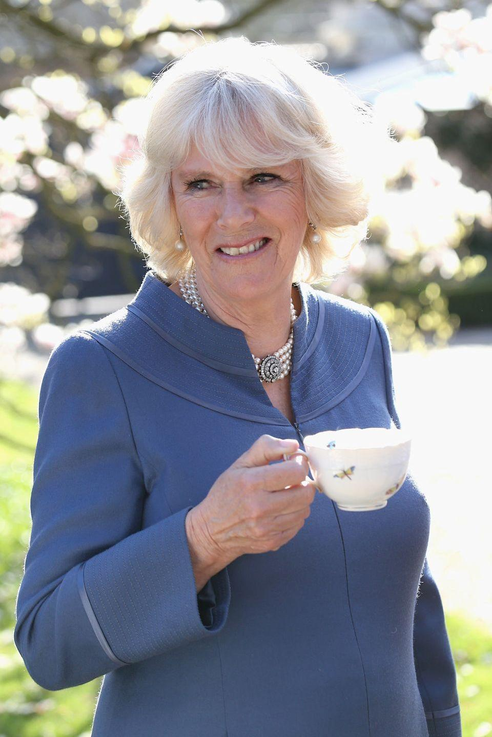 <p>Camilla enjoys a spot of tea outdoors in the Clarence House garden. She hosted a tea party to mark the fifth anniversary of First Story, a charity that supports creativity in UK secondary schools.<br></p>