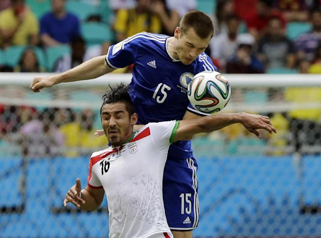 Iran's Reza Ghoochannejhad, front, is challenged by Bosnia's Toni Sunjic during the group F World Cup soccer match between Bosnia and Iran at the Arena Fonte Nova in Salvador, Brazil, Wednesday, June 25, 2014. (AP Photo/Sergei Grits)