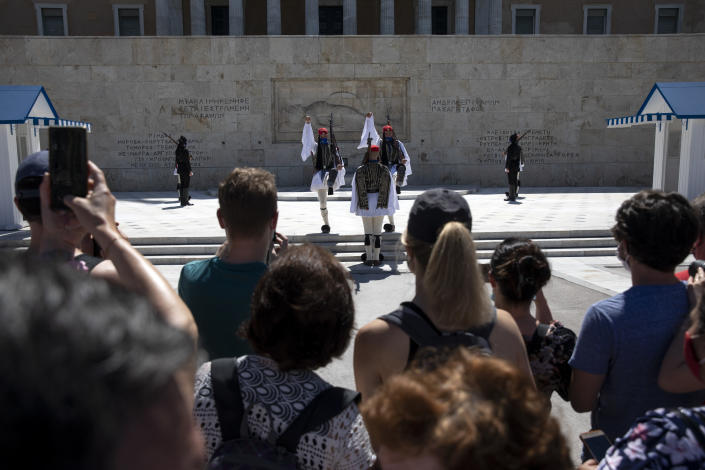 People watch a change of shift of Presidential guards, in Athens, Sunday, May 23, 2021. Greece launched its tourism season last week amid a competitive scramble across the Mediterranean to lure vacationers emerging from lockdowns. (AP Photo/Yorgos Karahalis)