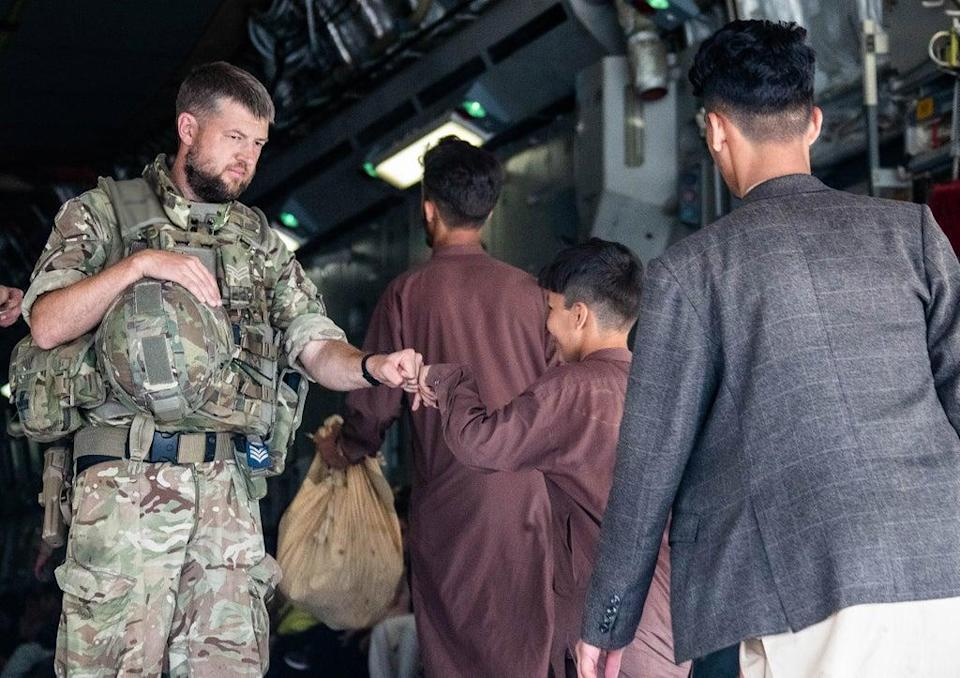 Handout photo issued by the Ministry of Defence (MoD) of a member of the UK Armed Forces fist-bumping a child evacuee at Kabul airport (LPhot Ben Shread/MoD) (PA Media)
