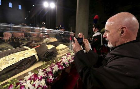 A friar takes a picture at the exhumed body of the mystic saint Padre Pio in the Catholic church of San Lorenzo fuori le Mura in Rome, February 3, 2016. REUTERS/Yara Nardi
