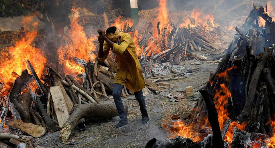 A man walks past the burning funeral pyres of those who died from the coronavirus during a mass cremation in New Delhi. (Reuters)