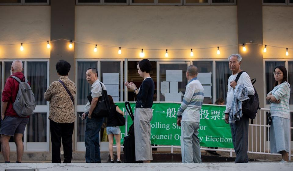 Voters queue to vote in the district council elections, but they will have no say in the choice of chief executive. Photo: EPA-EFE