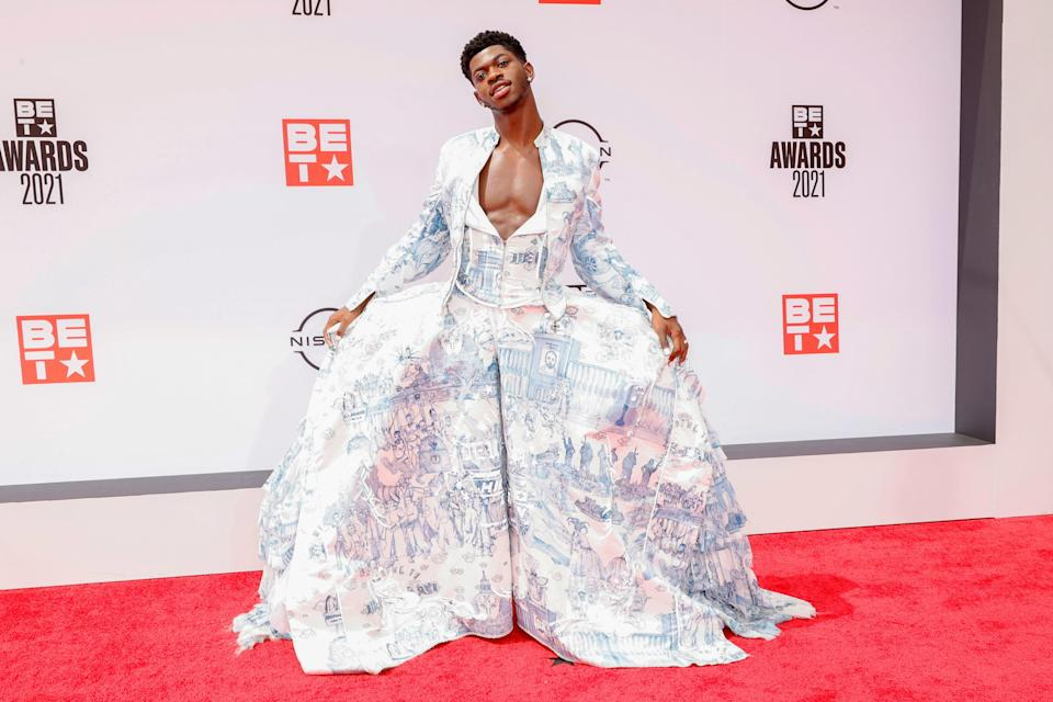 """Pulling out all the stops, as usual, Lil Nas X slipped into a """"historical dress"""" from Andrea Grossi's """"Welcome to Deusland"""" graduate collection. The dress (and matching biker jacket that Lil Nas X later took off) featured illustrations handmade by Grossi in delicate blue and white."""