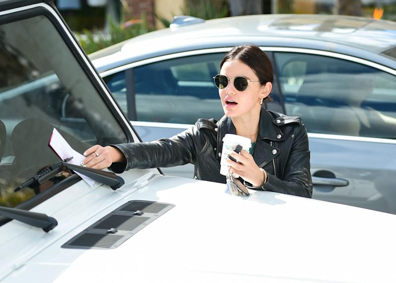 Lucy Hale picking up a parking fine off the windscreen of her car in Los Angeles.