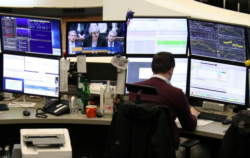 FILE PHOTO: A trader works at his desk at the stock exchange in Frankfurt