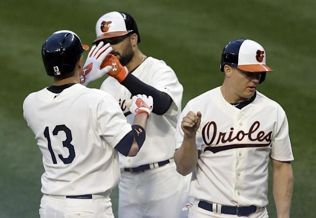 Baltimore Orioles' Manny Machado (13) high-fives teammates Nick Markakis, center, and Nick Hundley after driving them in on a home run in the second inning of an interleague baseball game against the St. Louis Cardinals, Friday, Aug. 8, 2014, in Baltimore. (AP Photo/Patrick Semansky)