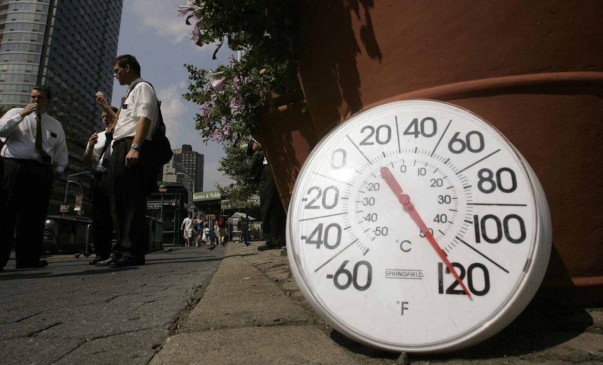 A thermometer in the sun on the sidewalk indicates a temperature of 120 degrees as people eat ice cream in New York City in August 2006 (Photo: Chris Hondros/Getty Images)