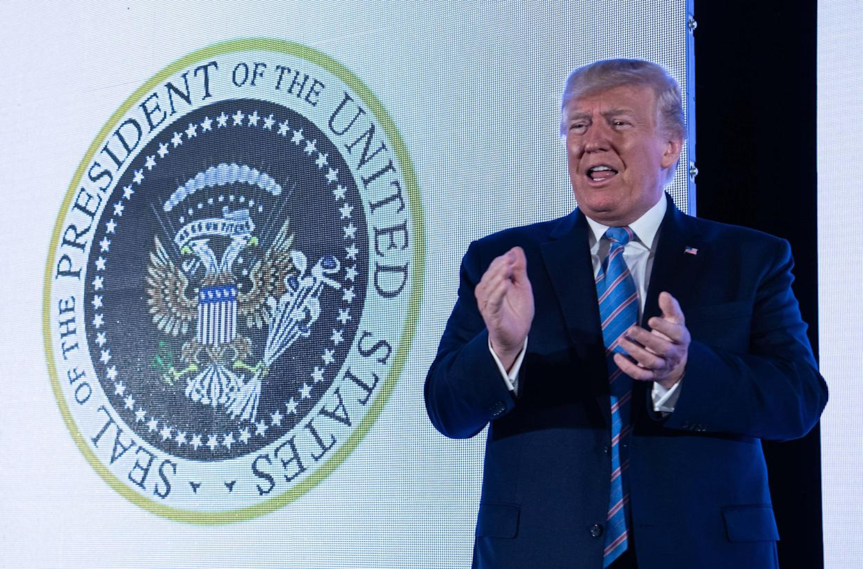 President Trump stands next to a surreptitiously altered presidential seal at Turning Point USA's student summit in Washington, D.C., on Tuesday. (Photo: Nicholas Kamm/AFP/Getty Images)
