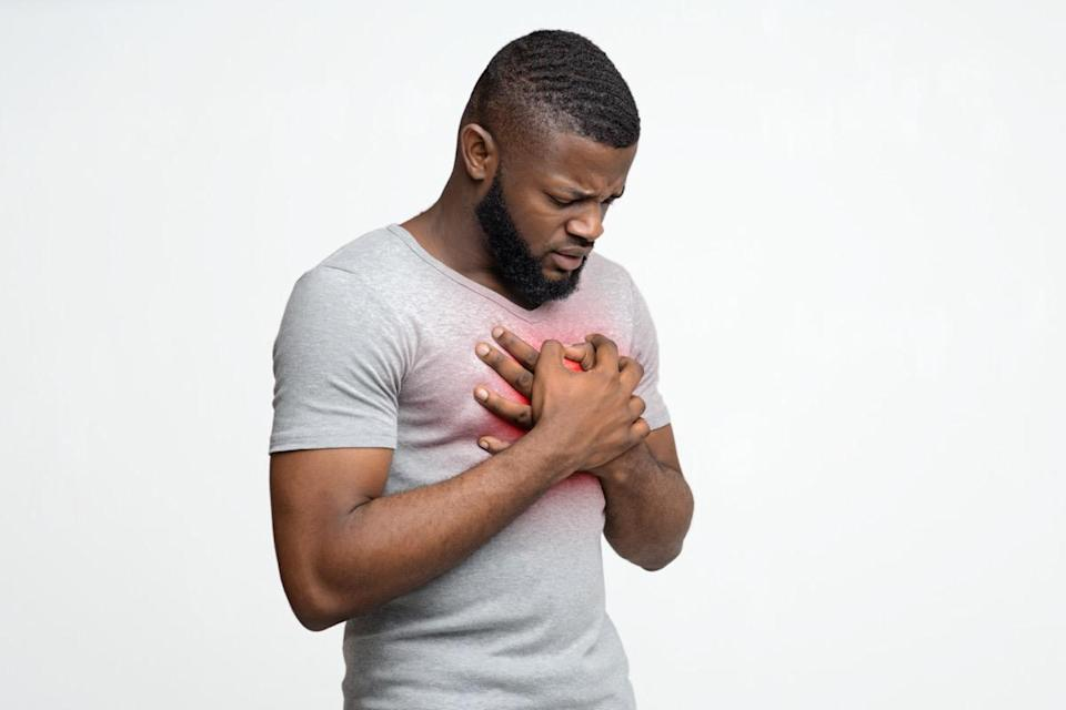Sad young black man rubbing his chest over white background, free space, heart disease in young age