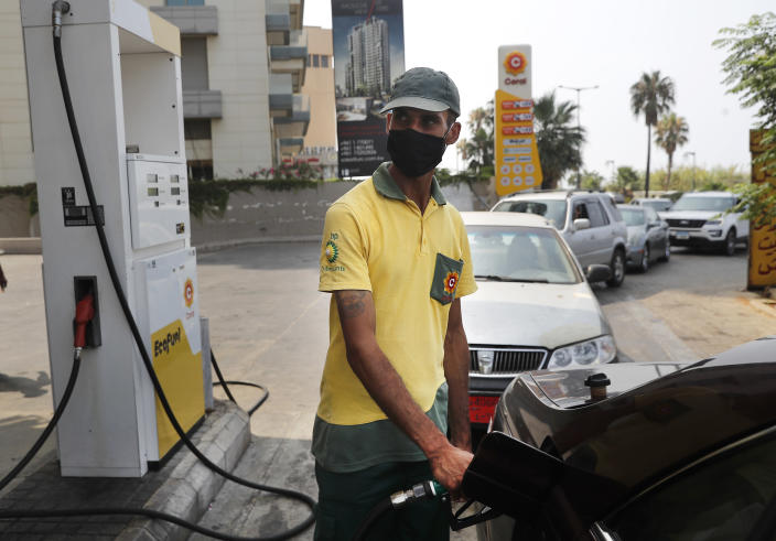 A gas station worker fills gasoline at a car, as other cars, background, line up amid fuel shortages, in Beirut, Lebanon, Wednesday, July 29, 2020. Lebanon is hurtling toward a tipping point at an alarming speed, driven by financial ruin, collapsing institutions, hyperinflation and rapidly rising poverty _ with a pandemic on top of that. The collapse threatens to break a nation seen as a model of diversity and resilience in the Arab world.(AP Photo/Hussein Malla)