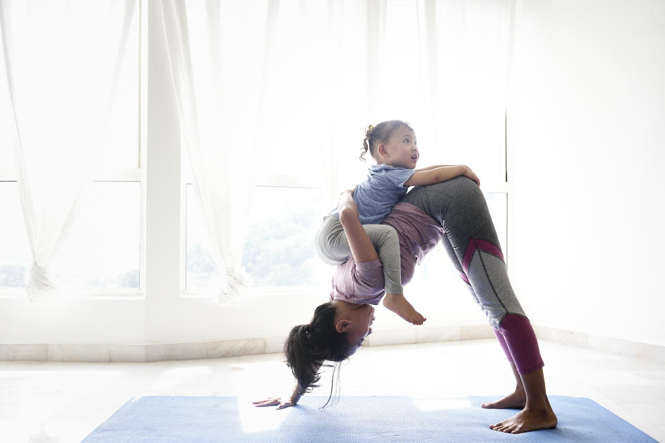 Woman doing yoga with daughter on her back