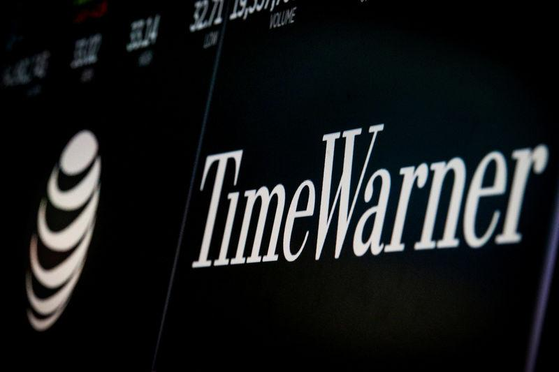 Logos and trading information for AT&T and Time Warner are displayed on a screen on the floor of the NYSE in New York