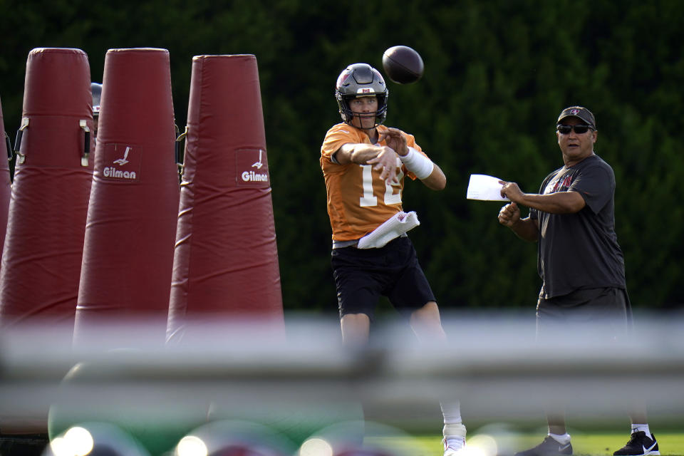 Tampa Bay Buccaneers quarterback Tom Brady (12) throws a pass as quarterbacks coach Clyde Christensen looks on during an NFL football practice Tuesday, July 27, 2021, in Tampa, Fla. (AP Photo/Chris O'Meara)