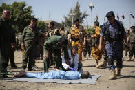 Policemen prepare a man convicted of involvement in the killing of a senior Houthi official Saleh al-Samad, to be executed at Tahrir Square in Sanaa, Yemen Saturday, Sept. 18, 2021. Yemen's Houthi rebels Saturday said they executed nine people for their alleged involvement in the killing of a senior Houthi official in an airstrike by the Saudi-led coalition more than three years ago. (AP Photo/Hani Mohammed)