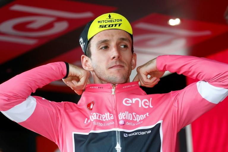 Simon Yates puts on the pink jersey after surviving attacks on the 18th stage