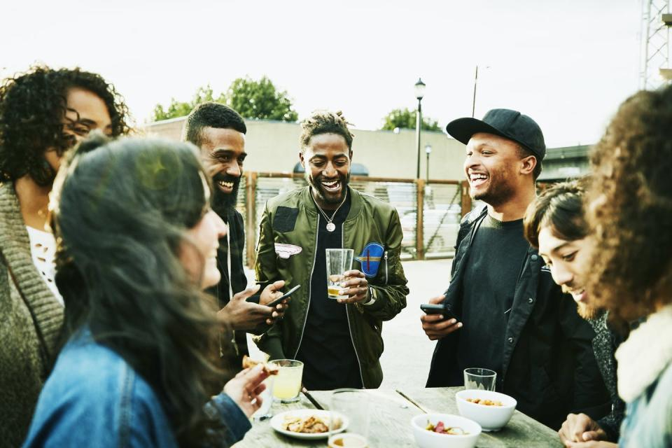 friends drinking and laughing at an outdoor bar