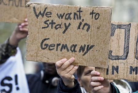 People hold signs during a pro-refugee demonstration in downtown Hamburg, Germany