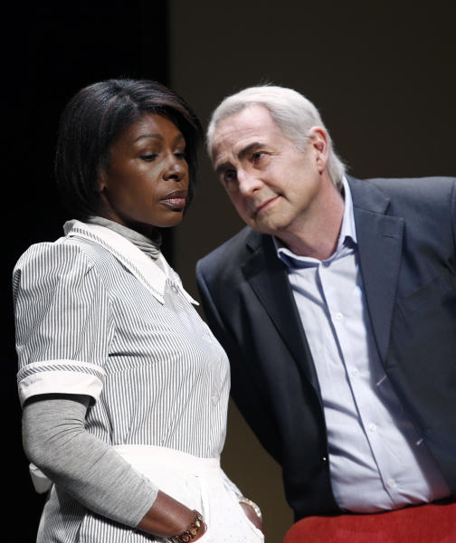 """FILE - In this Nov.15, 2012 file photo, French actor Eric Debrosse acting as former International Monetary Fund leader Dominique Strauss-Kahn, right, and actress Jelle Saminnadin acting as Nafissatou Diallo, the hotel housekeeper, who accused Dominique Strauss-Kahn of sexually assaulting her, pose during a photo opportunity as they perform in a play """"Suite 2806"""" in a Paris theatre. One-time French presidential hopeful Dominique Strauss Kahn has been to hell and back since he was charged, then acquitted in New York of making a hotel maid perform a sexual act in 2011. Now DSK will be treading the boards, in a salacious new play that recounts knock for knock what might have happened in the now infamous suite of the Manhattan Sofitel hotel. (AP Photo/Christophe Ena, File)"""