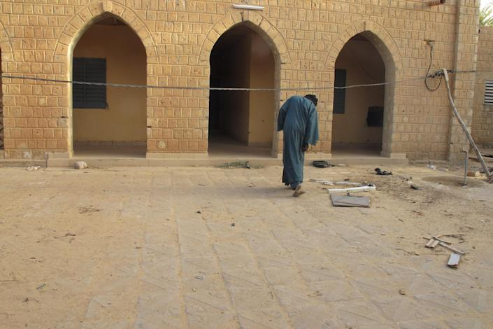 In this Wednesday, Feb. 6, 2013 photo, neighborhood resident Mohamed Alassane ducks under a wire to enter the Ministry of Finance's Regional Audit Department in Timbuktu, Mali, a site used by al Qaida-linked Islamists for more than a year. In the building, also used to hold European hostages, the AP found a more than 10-page letter signed by Abdelmalek Droukdel, the senior commander appointed by Osama bin Laden to run al-Qaida's branch in Africa. The confidential letter from the terror leader spelled out the terror network's blueprint for conquering this desert nation.(AP Photo/Rukmini Callimachi)