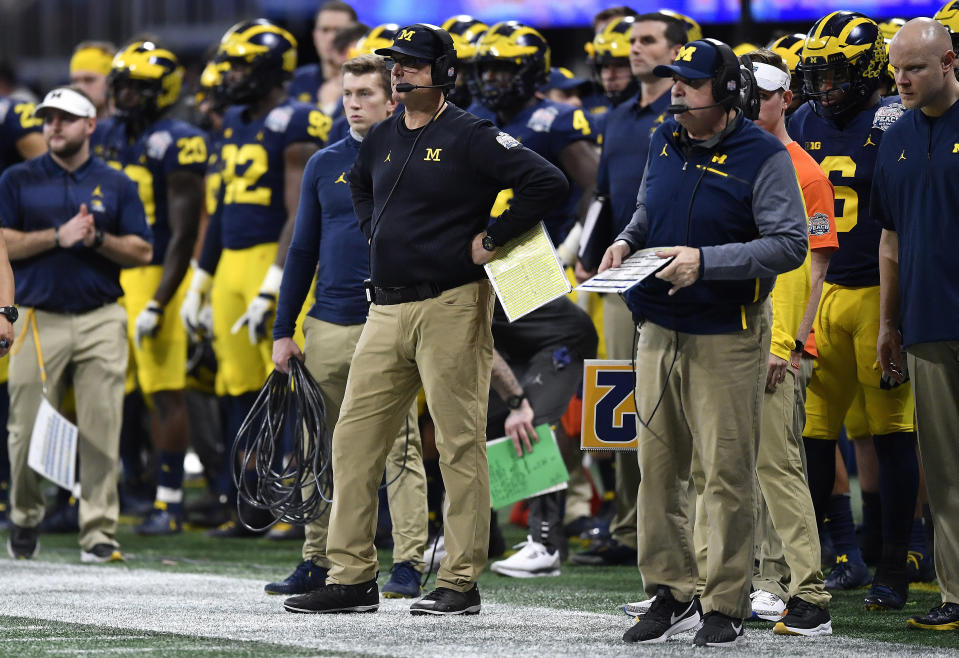 Michigan head coach Jim Harbaugh works during the second half of the Peach Bowl NCAA college football game against Florida, Saturday, Dec. 29, 2018, in Atlanta. Florida won 41-15. (AP Photo/Mike Stewart)