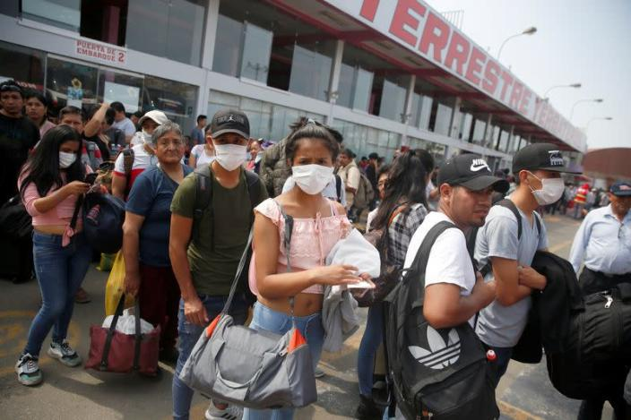 People wearing face masks wait to board a bus at a bus station after Peru's government deployed military personnel to block major roads, as the country rolled out a 15-day state of emergency to slow the spread of coronavirus disease (COVID-19), in Lima