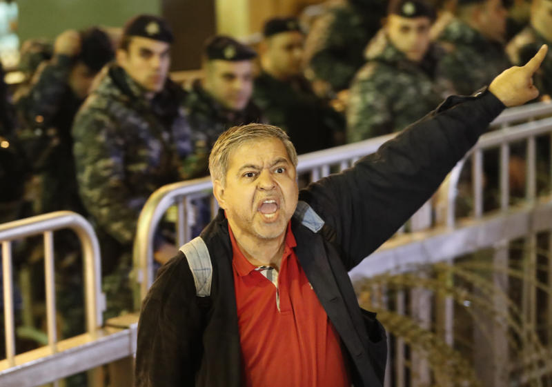 An anti-government protester shouts slogans, during ongoing protests against the ruling elite of corruption and financial crisis, in downtown Beirut, Lebanon, Wednesday, Dec. 18, 2019. Lebanon's caretaker prime minister said Wednesday he's no longer a candidate for the post, eliminating himself from consideration on the eve of scheduled consultations between the president and parliamentary blocs for naming a new premier. (AP Photo/Hussein Malla)