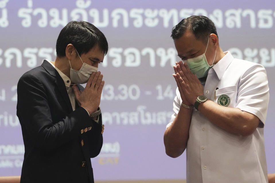 """Secretary General of The Chulabhorn Royal Academy Nithi Mahanonda, left, and Thailand's Public Health Minister Anutin Charnvirakul give the traditional greeting or """"wai"""" after a press conference in Bangkok, Thailand, Friday, May 28, 2021. The Chulabhorn Royal Academy, a Thai government research agency associated with the country's royal family said Friday it will purchase and import the Chinese-made COVID-19 vaccine Sinopharm, setting up a distribution channel separate from the government's free vaccination program. It said the first shipment of 1 million doses is supposed to be delivered in June, which should boost Thailand's lagging rate of vaccinations. (AP Photo/Sakchai Lalit)"""