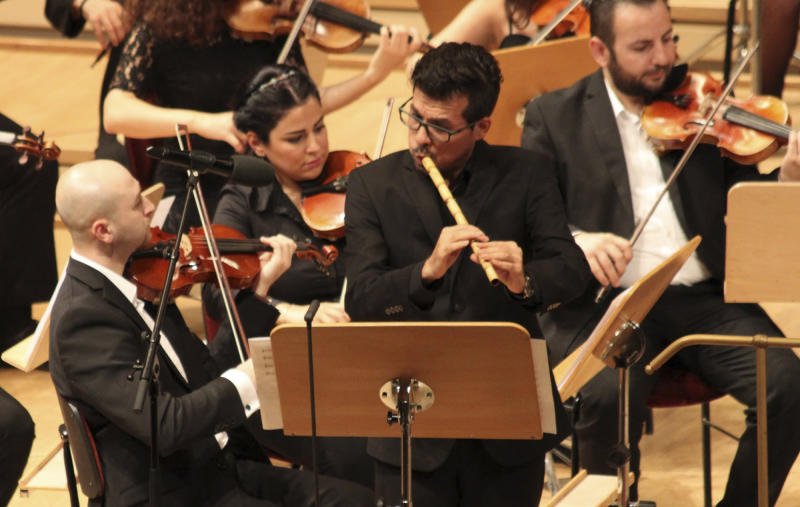 In this Sept. 11, 2016 photo Mohamad Fityan plays the Ney, a traditional Arabic flute, during a concert the Syrian Expat Philharmonic Orchestra in the Concert House in Berlin's Gendarmenmarkt. The Orchestra consists entirely of professional musicians who fled civil war in their homeland to seek refuge in Europe. (AP Photo/Jona Kallgren)