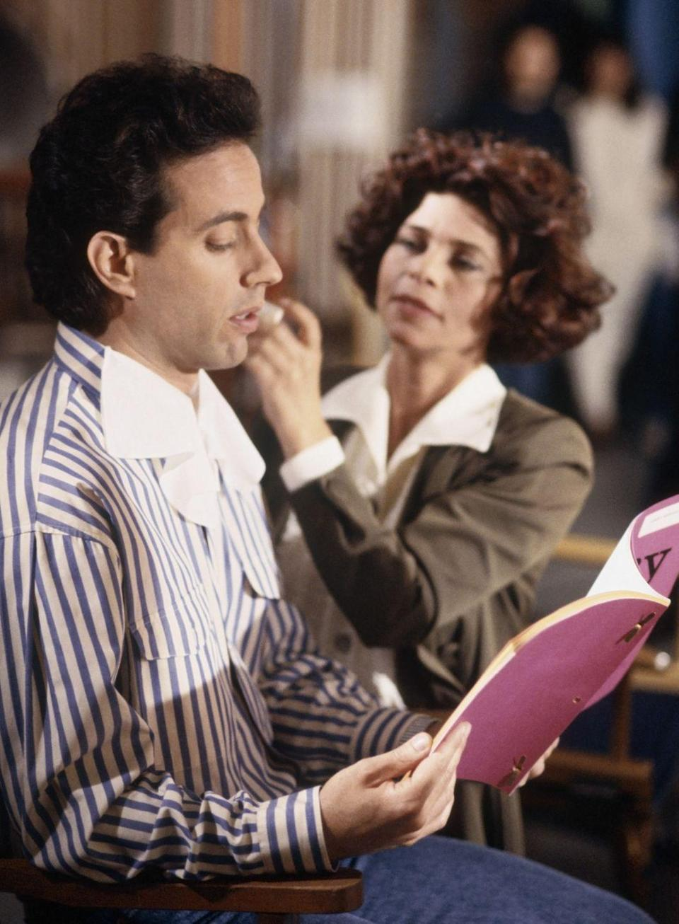 <p>Seinfeld prepares to tape an episode by reading through his lines in the hair and makeup chair. </p>