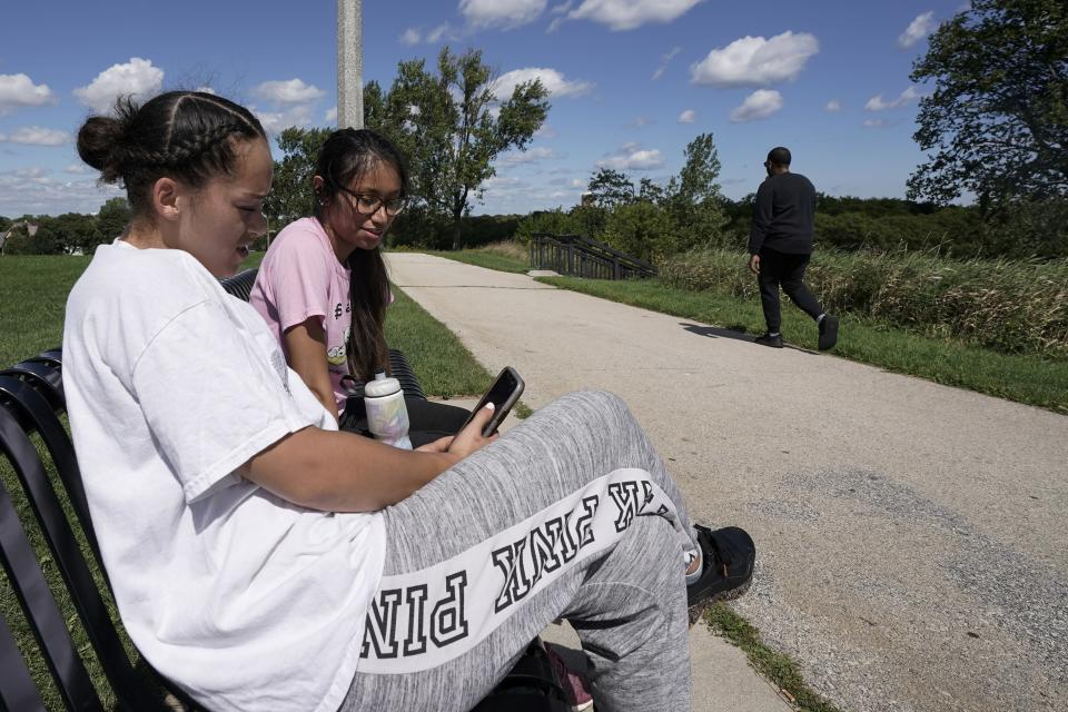 \Savannah Brown and Glendy Stollberg use their phone in Kilbourn Reservoir Park Wednesday, Sept. 8, 2021, in Milwaukee. The City of Milwaukee has placed wireless broadband hotspots in the park during the pandemic. (AP Photo/Morry Gash)