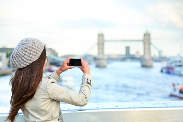 london-woman-tourist-taking-photo-on-tower-bridge-640x640
