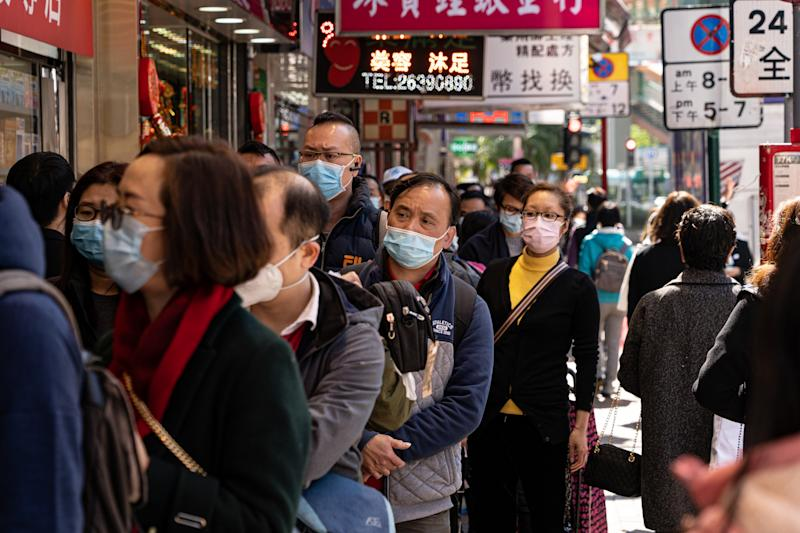 People wearing masks on the street in Hong Kong on January 30, 2020. People queue in line to purchase protective masks outside the store. (Photo by Yat Kai Yeung/NurPhoto via Getty Images)