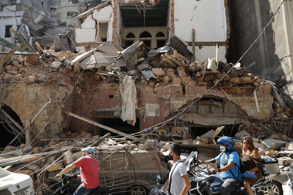Citizens ride their scooters and motorcycles pass in front of a house that was destroyed in Tuesday's massive explosion in the seaport of Beirut, Lebanon, Wednesday, Aug. 5, 2020. Residents of Beirut awoke to a scene of utter devastation on Wednesday, a day after a massive explosion at the port sent shock waves across the Lebanese capital, killing at least 100 people and wounding thousands. (AP Photo/Hussein Malla)